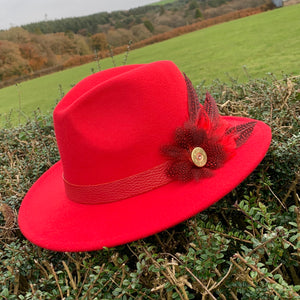 Poppy red fedora trimmed with feathers
