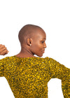 Bald girl with arms in air wearing Naturelle mustard long sleeve top