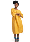 Woman wearing a yellow linen Godet dress by Baroque Clothing