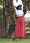 Female model standing outdoors wearing classic red culottes by Judith Atelier.