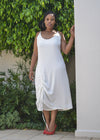Female model wearing white drawstring dress outdoors by Judith Atelier.