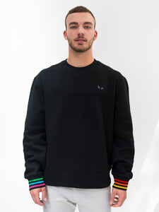 Cute model presenting black sweatshirt with rainbow sleeve cuffs