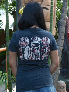 Girl looking at a Tiki in Mai-Kai Garden wearing a black tee shirt with three cannibals