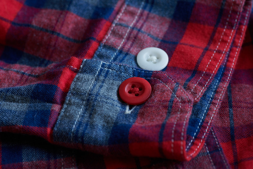 FRAHM LIGHTWEIGHT TARTAN WORKSHIRT CUFF WITH BRITISH COURTNEY'S COROZO BUTTONS. ONE BUTTON ON THIS SHIRT IS ALWAYS RED ON THE LEFT CUFF