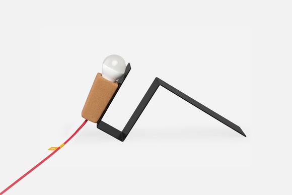 'Glint' is a desk lamp, with the perfect combination of two parts. A portable cork lightsource with magnets that allow the lamp to stick to any part of the metal surface. Available with a variety wire colours.