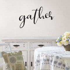 """The word, """"gather"""" on the wall behind a dining room table."""