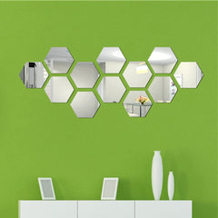 Bright green wall with hexagonal mirrored wall stickers on it.  Below is a white dresser with white items sitting on it.