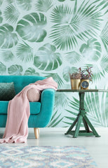 Light blue sofa with a rug in front, side table with a plant and clock on it, behind the sofa is a bold leafy accent wallpaper