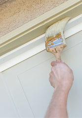 Hand holding a paint brush painting the trim of a door at an angle.