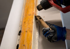 Close up of hands, one is holding a heat gun and another a scraper.  Both are removing paint off door trim.