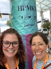 Photo of me and Marissa in front of a pillar with the HPMKT logo on it.