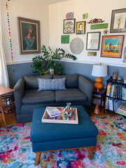 Living room with gray loveseat in the corner, the wall is painted gray below a chair rail and white above.  Colorful rug.