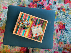 View from above of a teal ottoman with a rainbow tray.  Ottoman is sitting on a very bright and colorful rug