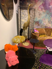 Showroom image of a black table with some felt dogs sitting on it, golden crane behind.