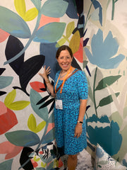 Me standing in front of a wallpaper that has large painted flowers.
