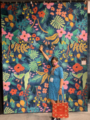 Me standing in front of a large rug designed by Rifle Paper Co.