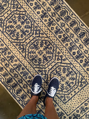 Photo of feet on a blue and white rug.