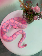 A pink snake accessory sitting on a table with some pink flowers next to it.