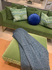 Velvet grass green sofa and ottoman with accent pillows and throw.