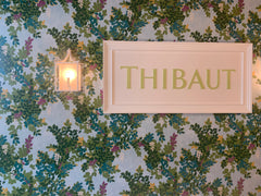 Thibaut signage on a floral wallpaper.