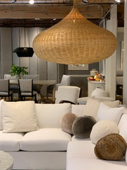 White sectional sofa with round ball pillows and above it is a large rattan light fixture.
