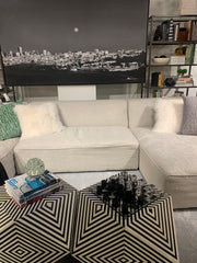 White sectional sofa, with a black and white cityscape photo behind it, and some cool geometric tables in front.