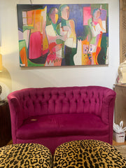 Magenta tufted loveseat with a colorful painting above it and 2 leopard print ottomans below.