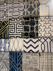 Various geometric designs on rugs that are hanging up.