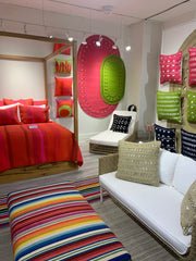 Canopy bed with hot pink bedding, an ottoman is in the forefront with colorful striped textile.