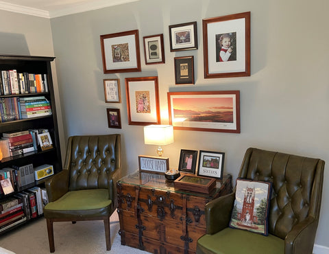 eclectic office space with bookshelf and placed wall art. two antique green leather chairs flanking an antique trunk.