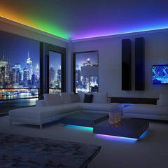 Living room with windows showing a city setting in the background, it's evening and there are neat LED lights in multiple colors along the wall molding and under the coffee tables