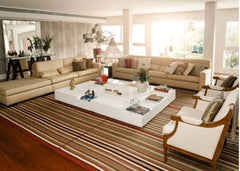 Large living room with a large floor rug under all of the furniture in the room.