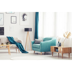 Living room with half a sofa showing, main part of photo is a teal chair with a table next to it.