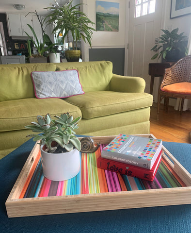 living room POV photo with multicolor wooden tray on a navy ottoman.