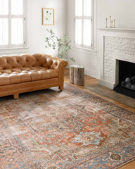 loloi terracotta sky rug in living room with fireplace and brown leather sofa