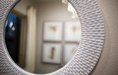 Close up of a round framed mirror on a wall, reflecting another wall with art on it.