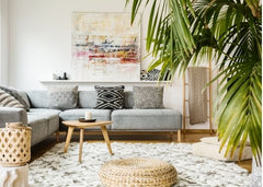 Living room with lots of natural materials used in the pillows, rugs and furniture.  There is also a large plant in the forefront of the photos