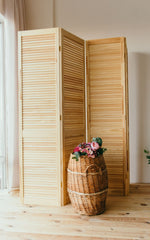 Light wooden slatted room divider with a basket in front filled with pink flowers.