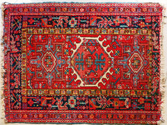 A small persian rug, mostly red with blue accents