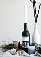 Black and white painted wine bottles, some natural branches, a pine cone and candle all set against a white backdrop