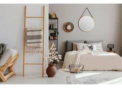 Bedroom in a simple design, in the forefront of the photos is a ladder with a blanket drooped over it.