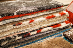 Close up of the edges of a stack of various rugs