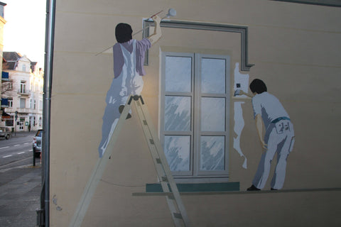 Outdoor mural of 2 people painting a window on the side of a building.