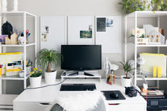Desk up against a wall, with two white bookcases on either side.  Large computer monitor on the desk.