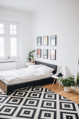White and bright bedroom, bed with white bedding.  Black and white rug on the floor.