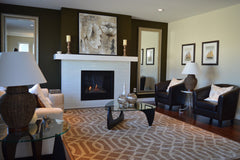 Neutral and brown living room, set up around a fireplace.
