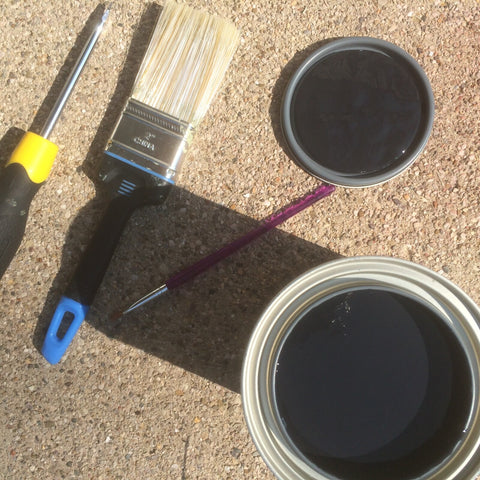 Open paint can with black paint, large paint brush, smaller paint brush and screwdriver.