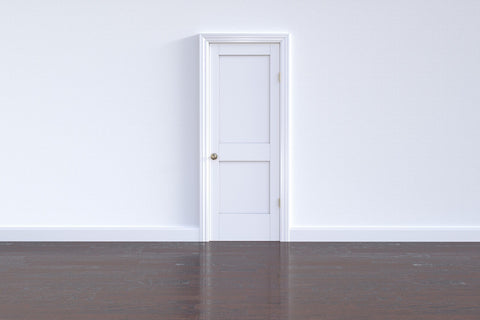 White wall with nothing but a white door, hardwood floors.  Entire room is empty