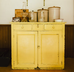 old yellow cabinet with jars on top
