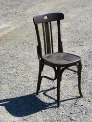 dark brown older style chair sitting outside